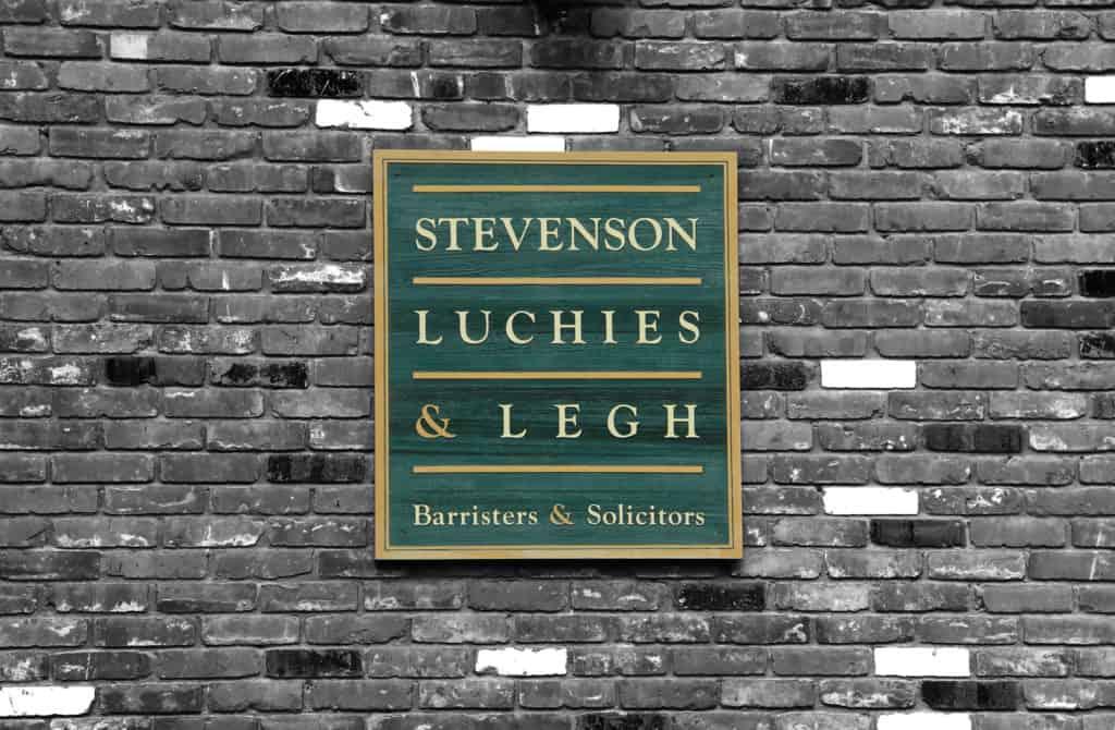 Stevenson Luchies and Legh logo on gray brick wall
